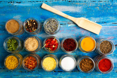 Large collection of spices in bowls on wooden table flat lay