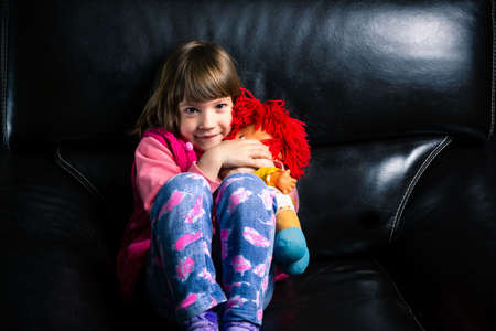 Cute girl with her toy on the sofa at home