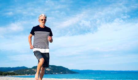 Senior man running on the beach, healthy lifestyle