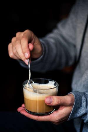 Man mixing a cup of coffe closeup