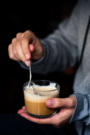 Man mixing a cup of coffe closeup