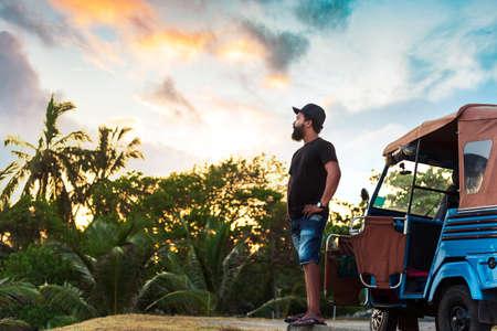Sri Lankan Man standing by the tuk tuk taxi at sunset Stock Photo