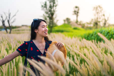 Woman having fun at a wheat field at sunset