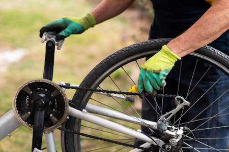 Man lubricating bicycle chain and maintaining for the new season 스톡 콘텐츠