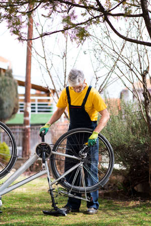 Man lubricating bicycle chain and maintaining for the new season 스톡 콘텐츠 - 124624260