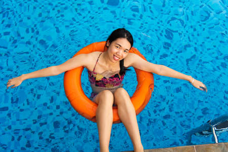 Girl enjoying at the swimming pool floating on water Stockfoto