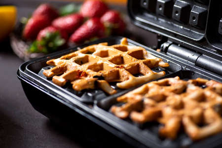 Waffle pastry baking on a waffle maker machine close up