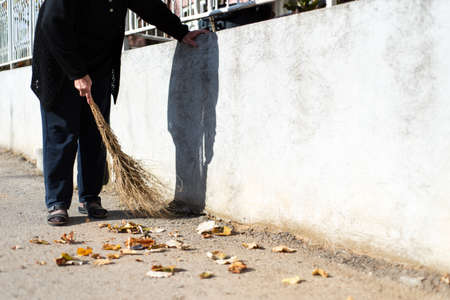 Senior woman cleaning fallen autumn leaves on the street Stock Photo
