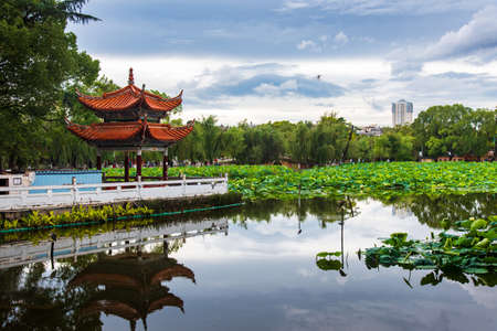 Chinese pavilion reflected in Green lake in Kunming, capital of Yunnan province of China
