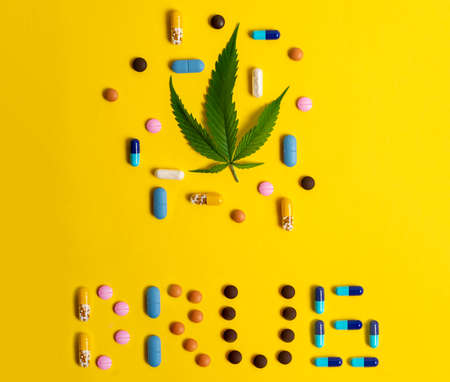 Cannabis leaf and the word drug written with pills Reklamní fotografie