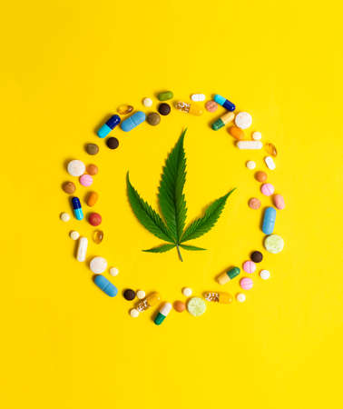 Cannabis leaf and many colorful pills on yellow background
