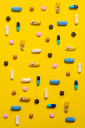 Various types of colorful pills on yellow background