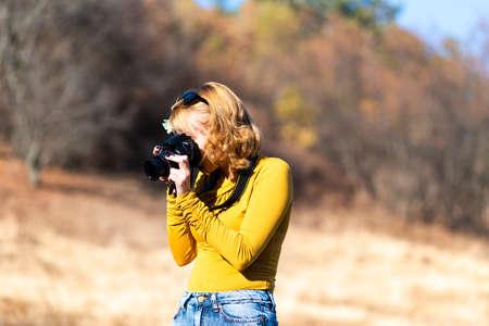 Female photographer capturing autumn scenery outdoors