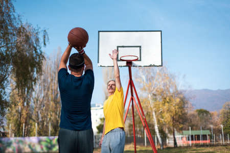 Father and son playing basketball in the park, family fun
