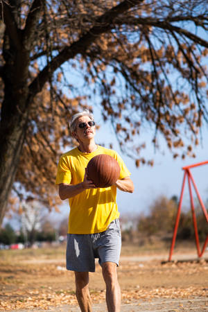 Senior man playing basketball in the park