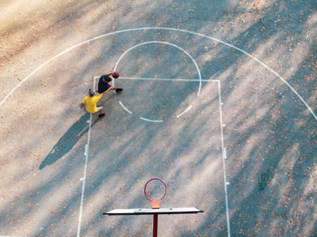 Father and son playing basketball in the park aerial view
