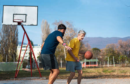Senior man playing basketball with his son in the park