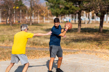 Senior father and son playing basketball in the park