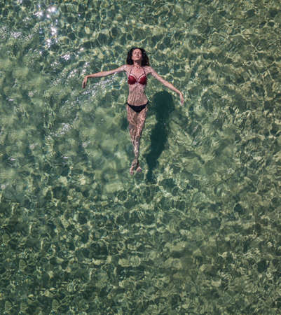 Girl lying on the water drone photo