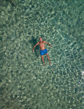 Chubby guy floating in the sea aerial Stock Photo