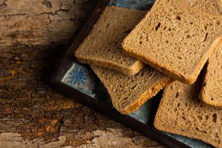 Brown rye bread slices on a wooden table top view Imagens