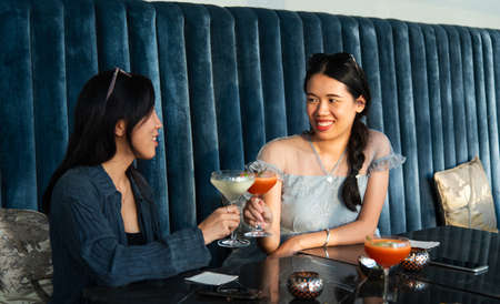 Asian girls toasting with cocktails at the bar