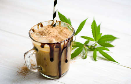 Cup of coffee with milk in a glass and marijuana leaves