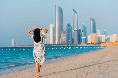 Female tourist on Abu Dhabi city beach with a view