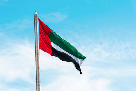 United Arab Emirates flag winding in the wind against blue sky