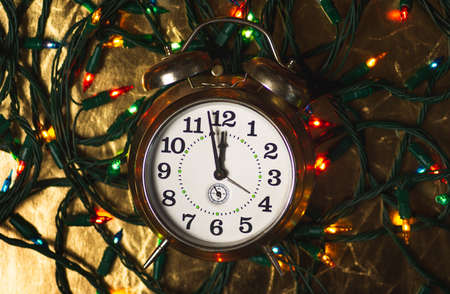 Vintage clock approaching midnight time and Christmas tree lights