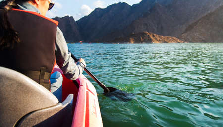 Woman kayaking in a scenic lake surrounded by mountains , active lifestyle Stock fotó