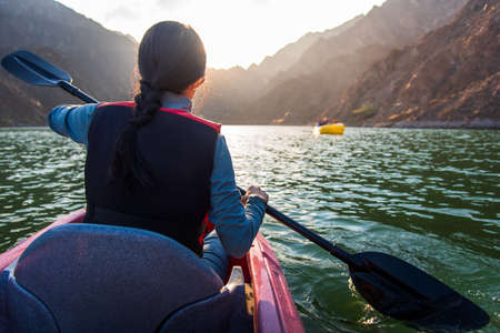 Woman kayaking in scenic Hatta lake in Dubai at sunset Stock fotó