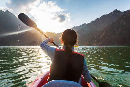 Woman kayaking in a mountain surrounded lake at sunset Stock fotó
