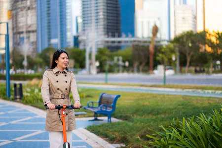 Woman using electric scooter for transportation in a modern city environment Stock Photo