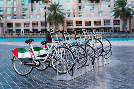 Dubai, United Arab Emirates - December 11, 2018: Rental bicycles used for sightseeing with UAE flag in Dubai