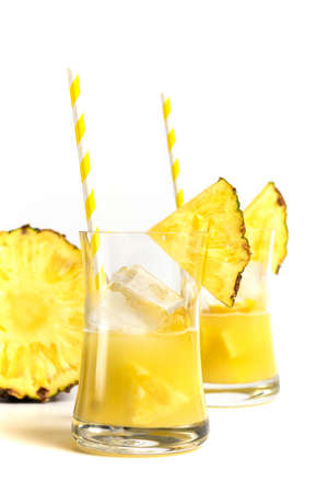 Glass of pineapple juice with a straw and slices of pineapple isolated on white background