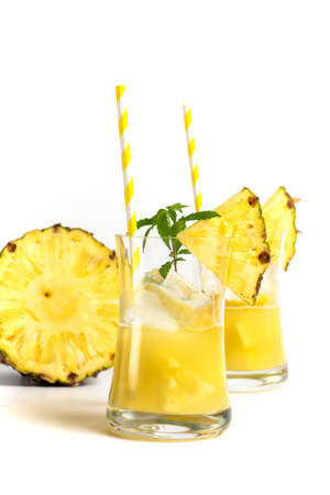 Glass of pineapple juice with a straw and slices of pineapple isolated on white background Reklamní fotografie
