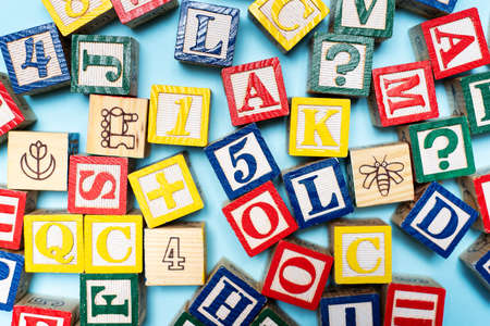 Alphabet characters written with wooden letters, education abstract background top view
