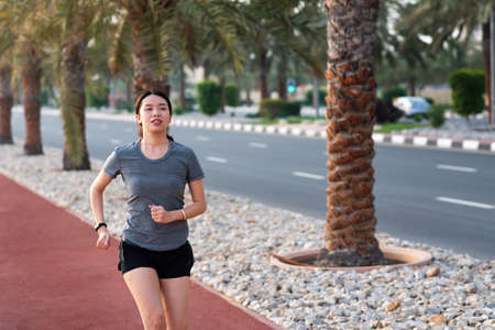 Asian woman jogging on the running track outdoors to maintain fitness active lifestyle