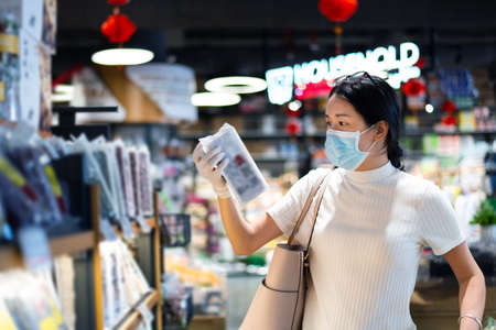 Asian woman shopping for groceries in the market wearing mask and gloves to prevent virius spread during coronavirus pandemic Imagens