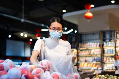 Asian woman shopping for fruit in the market wearing mask and gloves to prevent virus spread during coronavirus pandemic