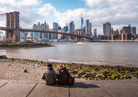 Young couple watching the Brooklyn bridge and lower Manhattan in the winter