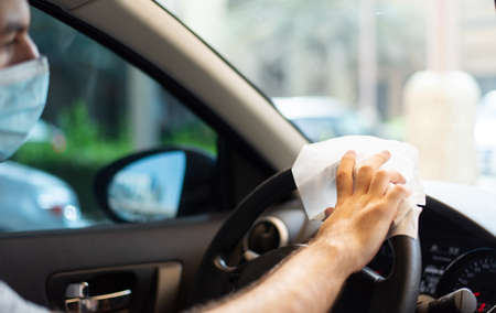 Man cleaning his car steering wheel for disinfection and a safe ride during the virus pandemic closeup Reklamní fotografie