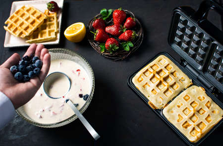 Chef adding fruit in waffles dough close up