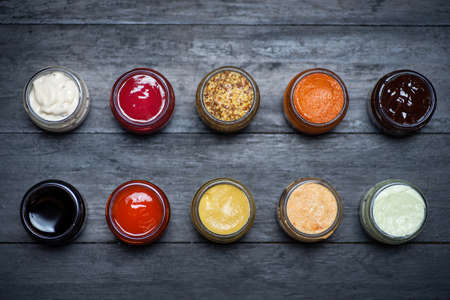 Large collection of sauces and spiced spreads in small jars as mayo ketchup mustard soy sauce and many more