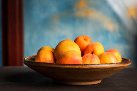Ripe Apricot fruit isolated on a wooden table in a bowl closeup