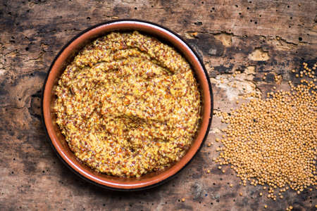 Wholegrain mustard in a wooden bowl on a table tabletop