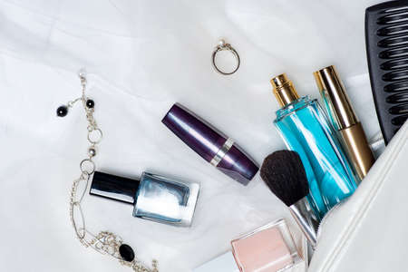 Various makeup and cosmetic fall out of an female bag tabletop flat lay. Perfume lipsticks nail polishes with brushes an other accessories Stok Fotoğraf