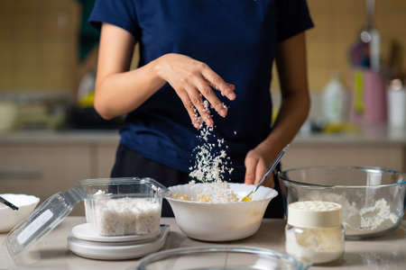 Woman adding grated coconut into cookie dough while making homemade cookies in the kitchen at home closeup Stok Fotoğraf