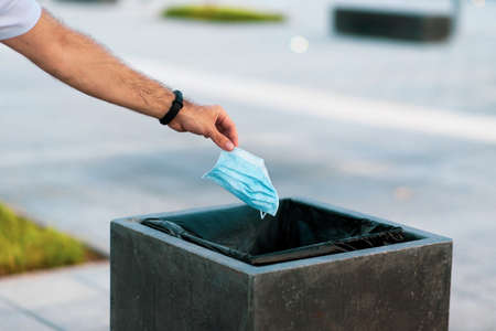 Man throwing used disposable protective surgical mask into the garbage bin closeup